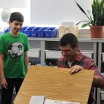 A Room 5 student shows his visitor his classroom and desk