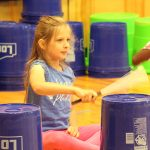 A Room 2 student demonstrates her percussion skills during All School Assembly