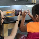 A student prepares her bottle rocket in science