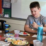 Students enjoy fruit, crackers, and cheese during their Conversation Party!