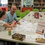 Families and students take a quiet moment at the coloring station