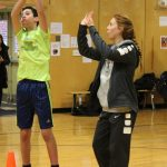 A visiting player offers a Wolf student tips on shooting