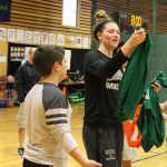 A Brown basketball player distributes jerseys for a 3 on 3 game